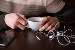 Tasse Tee, Kopfhörer und Telefon Lizenzfreie Stockbilder