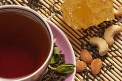 Tasse Tee, Mandeln, Muttern und Traubenzucker Stockfotografie