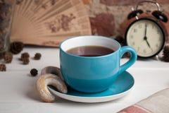 Tasse Tee mit Biskuiten Fünf O-Borduhr stockbilder