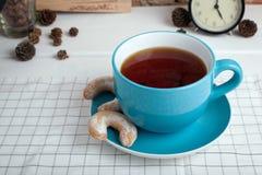 Tasse Tee mit Biskuiten Fünf O-Borduhr lizenzfreie stockbilder