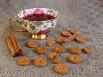 Tasse Tee mit Crackern und Zimt auf Tischdecke Stockfotografie