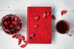 Tasse Tee mit einem Buch und rosafarbenen Blumenblättern Stockfoto