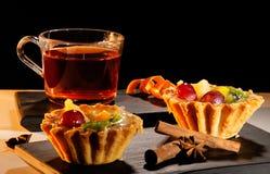 Tasse Tee mit einem Kuchen, einem Zimt und einem Anis auf Behälter stockbilder