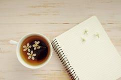 Tasse Tee mit Frühlingsblumen und -notizbuch Lizenzfreies Stockbild