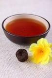 Tasse Tee mit gelber Blume auf Leinenserviette lizenzfreies stockbild
