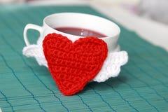 Tasse Tee mit Häkelarbeitherzen stockfoto