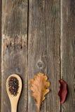 Tasse Tee mit Herbstlaub auf hölzernem Hintergrund stockbild