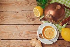 Tasse Tee mit Ingwer-, Zitronen- und Teetopf auf Holztisch Ansicht von oben Stockbilder