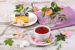 Tasse Tee mit Käsekuchen und wilder rosafarbener Blume auf altem hölzernem Hintergrund Stockfoto