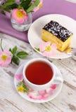 Tasse Tee mit Käsekuchen und wilder rosafarbener Blume auf altem hölzernem Hintergrund Lizenzfreies Stockfoto