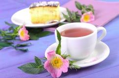 Tasse Tee mit Käsekuchen und wilder rosafarbener Blume auf purpurroten Brettern Lizenzfreie Stockbilder