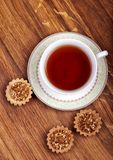 Tasse Tee mit Kuchen auf einem hölzernen Hintergrund Stockbild