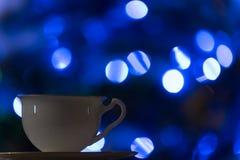 Tasse Tee mit Lichtern des neuen Jahres lizenzfreies stockbild