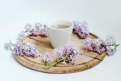 Tasse Tee mit lila Frühling blüht auf der hölzernen Tabelle Weißer Hintergrund Stockfotos