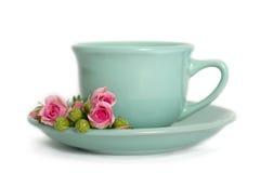 Tasse Tee mit rosafarbenen Blumen isoleted auf Weiß Stockfotografie