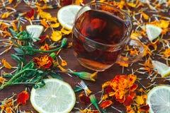 Tasse Tee mit Scheiben der Zitrone und der Blumen Stockbild