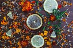 Tasse Tee mit Scheiben der Zitrone und der Blumen Lizenzfreie Stockfotos