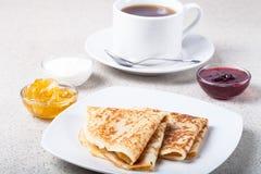 Tasse Tee mit Stau, Sauerrahm und russischen Pfannkuchen - Blini Lizenzfreies Stockbild