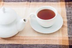 Tasse Tee mit Teekanne auf Tabelle Stockfoto