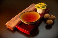 Tasse Tee mit Walnüssen und Blumen Stockfotografie