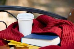Tasse Tee oder coffe mit blauem Buch Nd des roten Schals auf dem Tisch Lizenzfreies Stockfoto