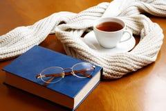 Tasse Tee, Schal? Gläser und Buch Stockbilder