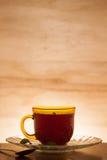 Tasse Tee schoss gegen einen hintergrundbeleuchteten hölzernen Hintergrund lizenzfreies stockbild
