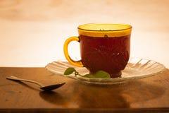 Tasse Tee schoss gegen einen hintergrundbeleuchteten hölzernen Hintergrund stockbild