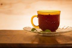 Tasse Tee schoss gegen einen hintergrundbeleuchteten hölzernen Hintergrund lizenzfreie stockfotografie