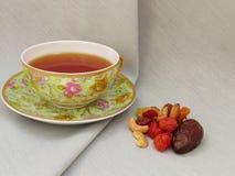 Tasse Tee Trockenfrüchte und Nüsse Stockfoto