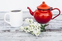 Tasse Tee und alte rote Teekanne auf Weinleseholztisch mit Niederlassung der Flieder Stockbild