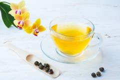 Tasse Tee und Bälle des grünen Tees Stockbild