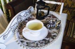 Tasse Tee und Bonbons auf einer Weinleseteetabelle Stockbilder