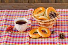 Tasse Tee und Donut auf einer Serviette in einem Käfig Stockbild