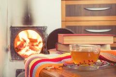 Tasse Tee und Flammen des Feuers in einem Kamin Lizenzfreie Stockfotos
