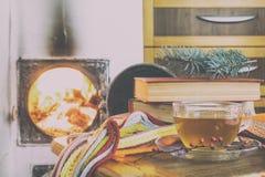 Tasse Tee und Flammen des Feuers in einem Kamin Stockbild