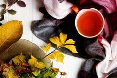 Tasse Tee und Herbstlaub auf einem weißen Holztisch Stockfotografie