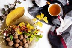 Tasse Tee und Herbstlaub auf einem weißen Holztisch Lizenzfreie Stockbilder