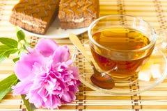 Tasse Tee und rosa Blume Lizenzfreie Stockfotos