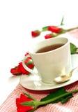 Tasse Tee und Rotrosen auf Weiß Lizenzfreie Stockfotos