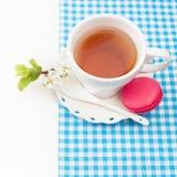 Tasse Tee und süße und bunte französische Makrone und eine Kirsche stockfotos