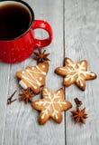 Tasse Tee und Weihnachtsplätzchen auf dem hölzernen Hintergrund Stockfotografie