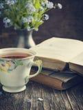 Tasse Tee, Weinlesebücher und Sommer blüht auf dem Tisch Lizenzfreie Stockfotografie