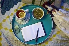 Tasse Tee, Zitrone, Glas Creme, Notizbuch, Stift, handgemachte Puppe stockfoto