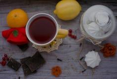 Tasse Tee, Zitrone, Mandarine und Meringe auf dem Tisch Lizenzfreie Stockbilder