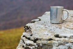 Tasse thermo d'acier inoxydable sur une pierre plate images stock