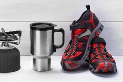Tasse thermo et chaussures rouges pour voyager sur un fond gris-clair photos libres de droits