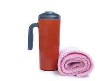 Tasse thermo orange et écharpe tricotée par rose photographie stock