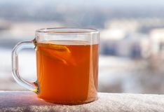 Tasse transparente avec la boisson, le citron et l'orange épicés chauds sur le fond de la ville d'hiver Images stock