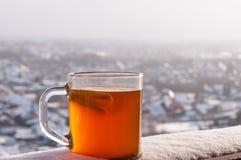 Tasse transparente avec la boisson, le citron et l'orange épicés chauds sur le fond de la ville d'hiver Image stock